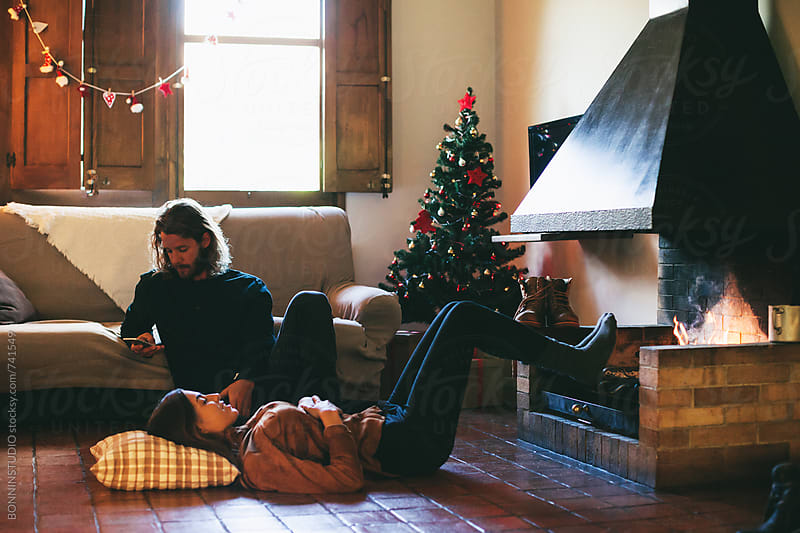 Couple resting by the fireplace on winter. by BONNINSTUDIO for Stocksy United