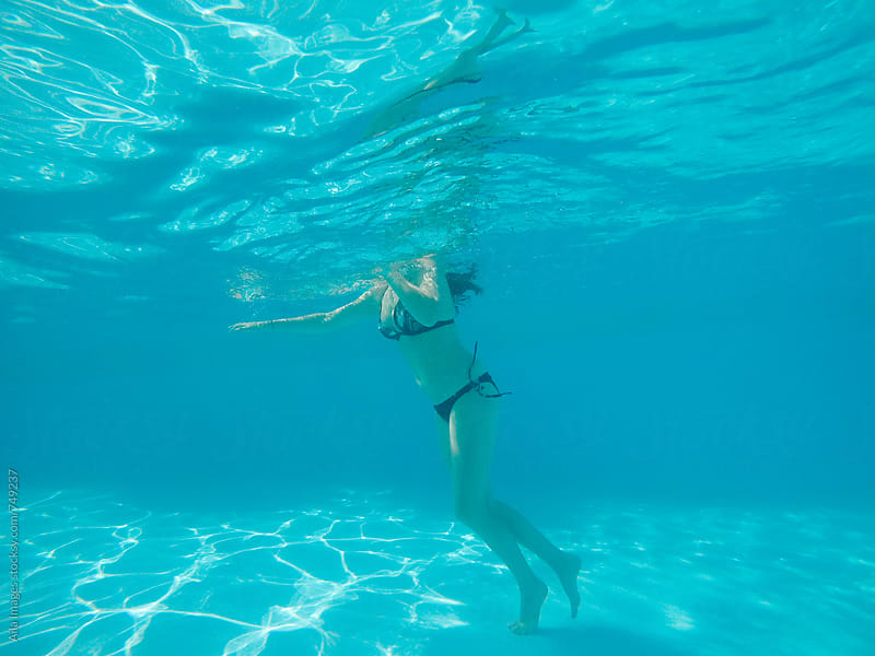 Woman swimming in a blue pool by Aila Images for Stocksy United