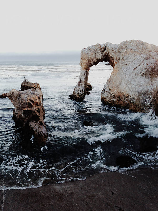 Dark Waves Under Ocean Arch by Kevin Russ for Stocksy United