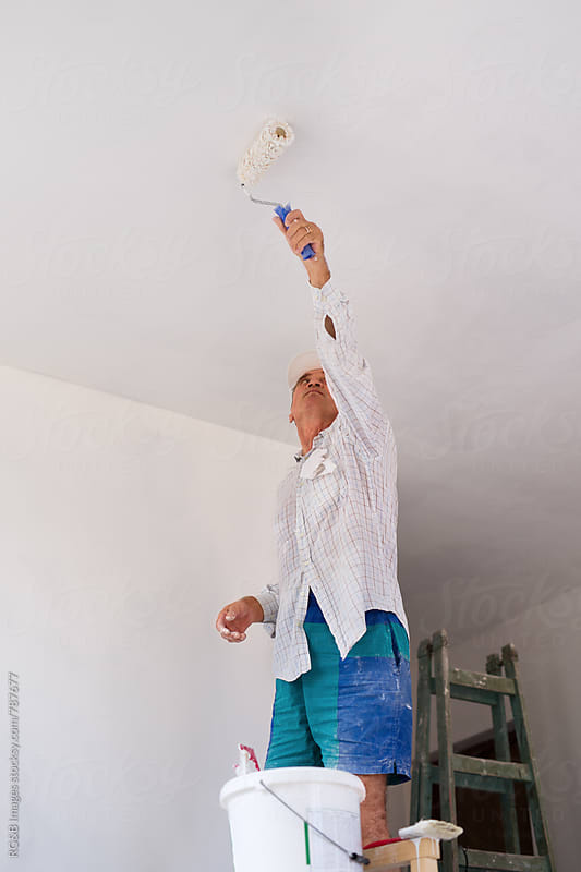 Craftsman painting the indoor walls white by RG&B Images for Stocksy United
