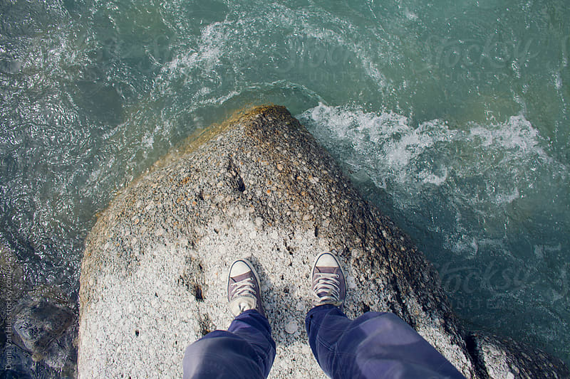 Person standing on a rock looking down in the middle of a river by Denni Van Huis for Stocksy United