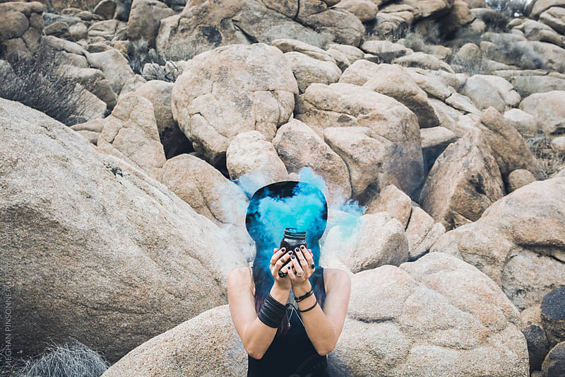 Woman Holding Blue Smoke Obscuring Face by MEGHAN PINSONNEAULT for Stocksy United