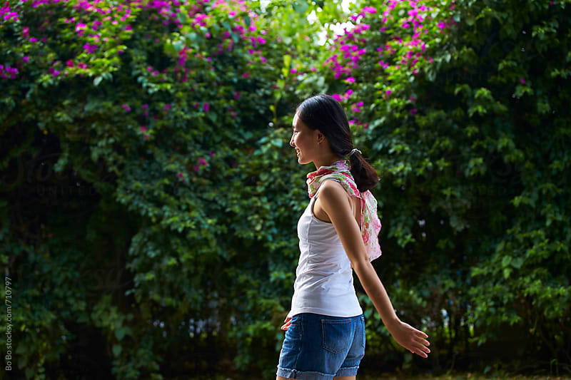 sideview of young asian woman walking outdoor by Bo Bo for Stocksy United