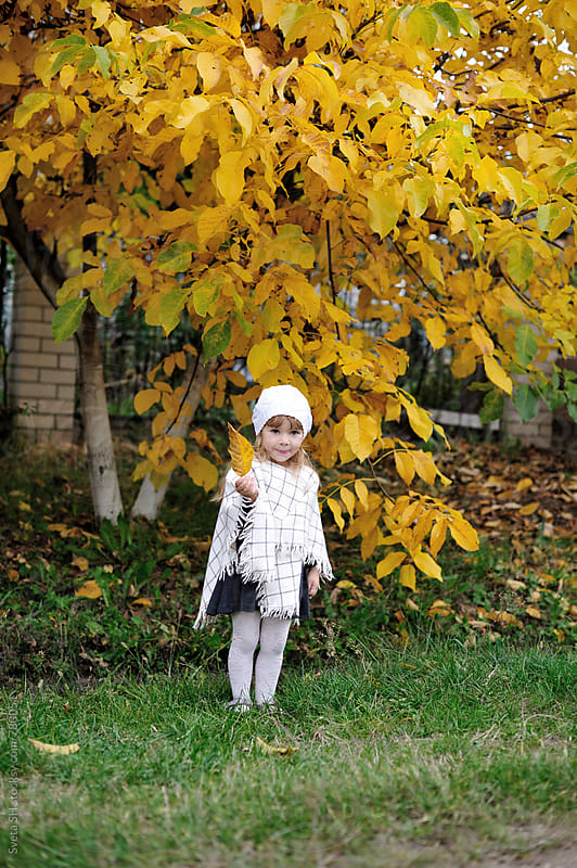 The little girl in a white poncho by Svetlana Shchemeleva for Stocksy United