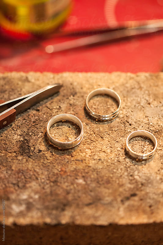 Golden wedding bands in a jewelry workshop.  by Mosuno for Stocksy United