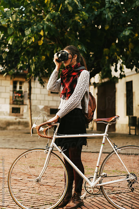 Tourist female with her vintage bicycle taking photos of the city. by BONNINSTUDIO for Stocksy United