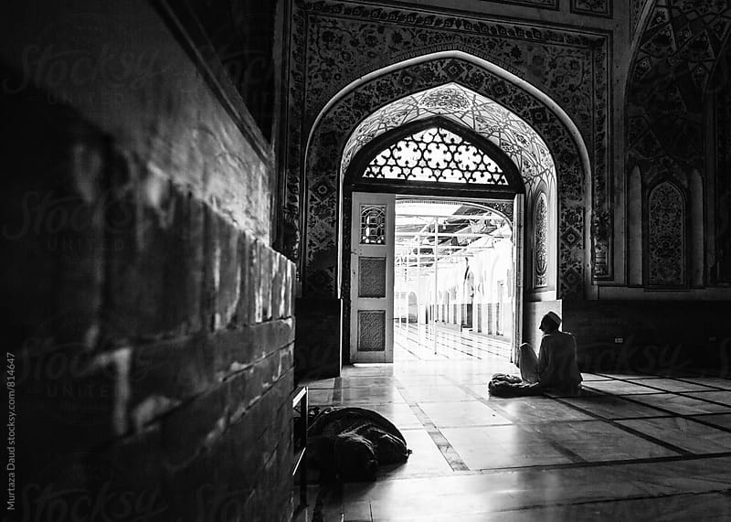 An old man sitting in a mosque with his belongings by Murtaza Daud for Stocksy United