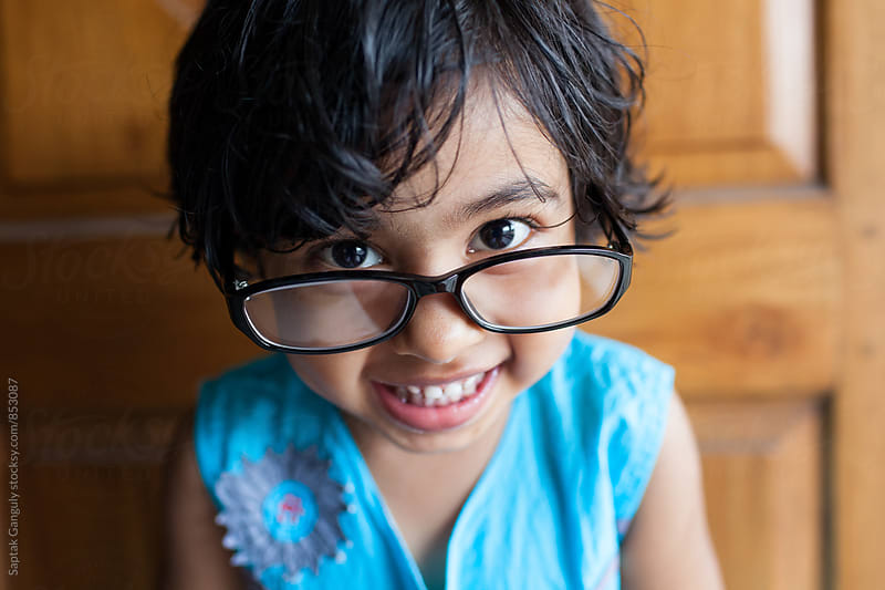 Portrait of a cute little girl with glasses smiling by Saptak Ganguly for Stocksy United