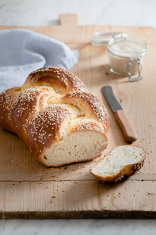 Challah, a braided bread, cut into slices by Laura Adani for Stocksy United