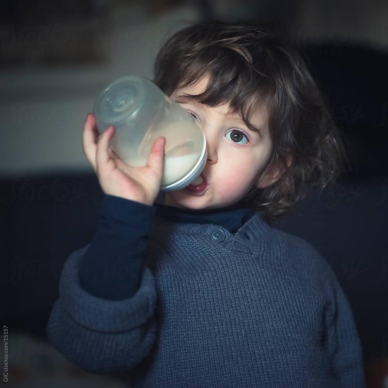 Little girl drinking milk from a baby bottle by Simone Becchetti for Stocksy United