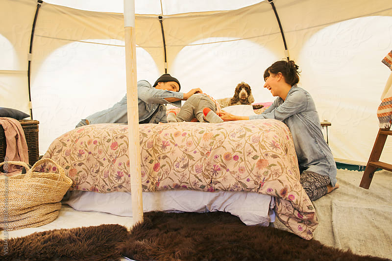 Glamping - Caucasian Family of Three Having Fun on Bed Inside Large Circular Tent by VISUALSPECTRUM for Stocksy United