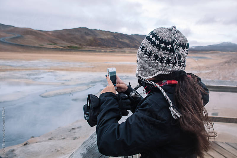 Woman taking a picture at Hverarond geothermal site, Iceland by Luca Pierro for Stocksy United