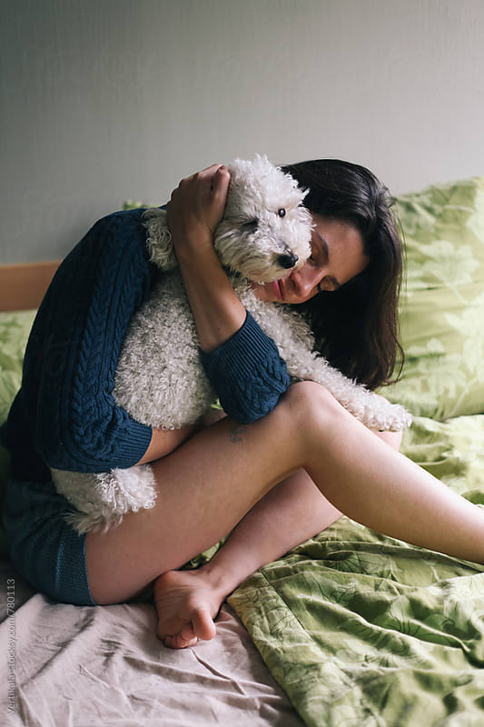 Brunette woman hugging with her white poodle on the bed  by Marija Mandic for Stocksy United