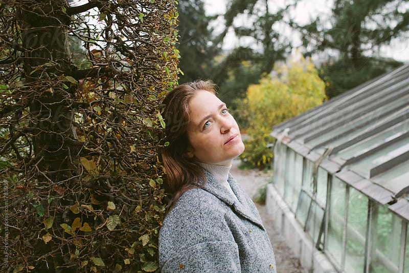 Woman leaning her head against a hedge in a botanical garden. by Julia Forsman for Stocksy United