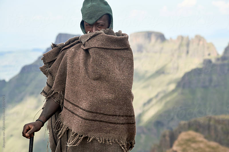 A portrait of a Monsotho shepherd dressed in traditional blanket standing against a wild  by Jacques van Zyl for Stocksy United