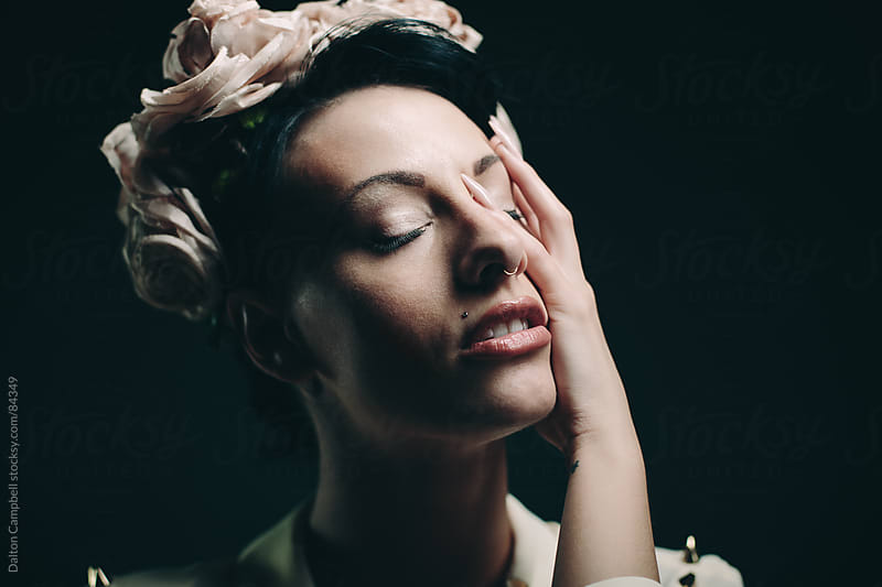 Young woman posing introspectively with flower headband.  by Dalton Campbell for Stocksy United