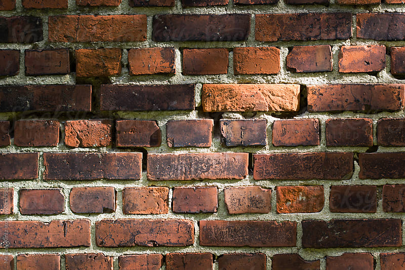 Background, brickwall with diagonal line of light by Melanie Kintz for Stocksy United
