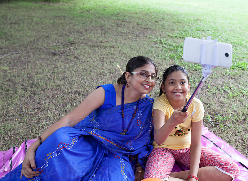 Mother and daughter taking selfie with selfie stick and smartphone by PARTHA PAL for Stocksy United