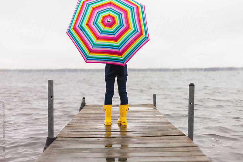Girl standing on dock with rainbow umbrella by Amanda Worrall for Stocksy United