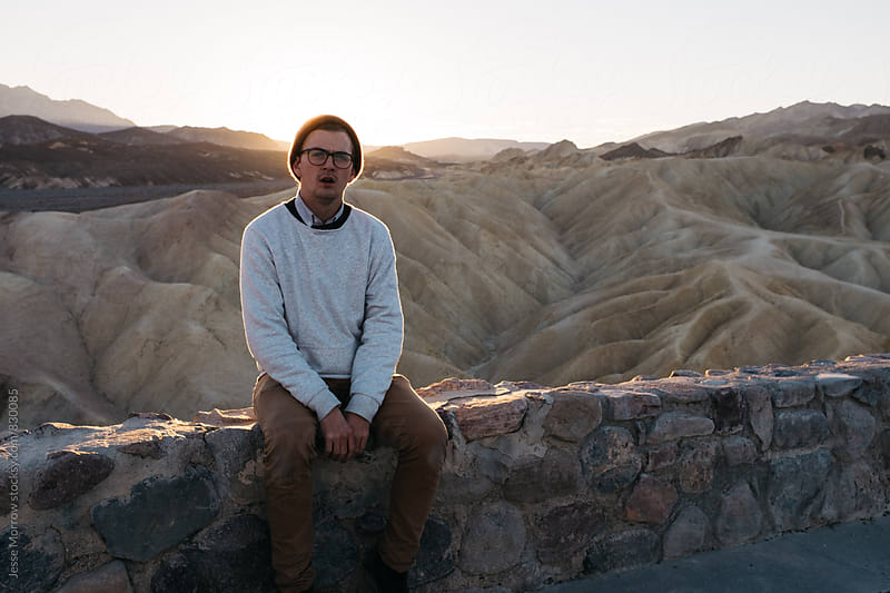 portrait of male wearing white fashionable sweater at sunrise in nature by Jesse Morrow for Stocksy United