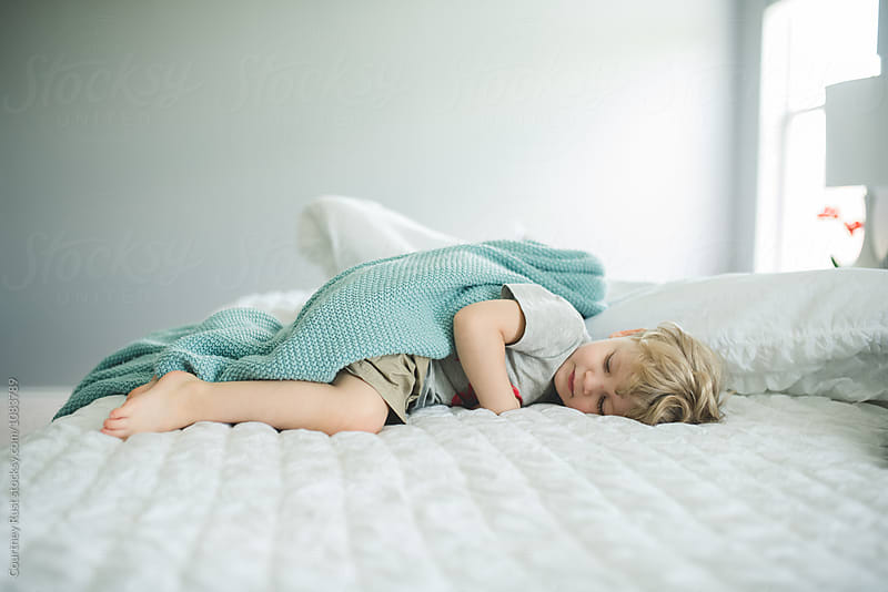 Boy napping in a white bed by Courtney Rust for Stocksy United