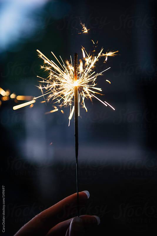Woman holds burning sparkler at dusk by Cara Dolan for Stocksy United
