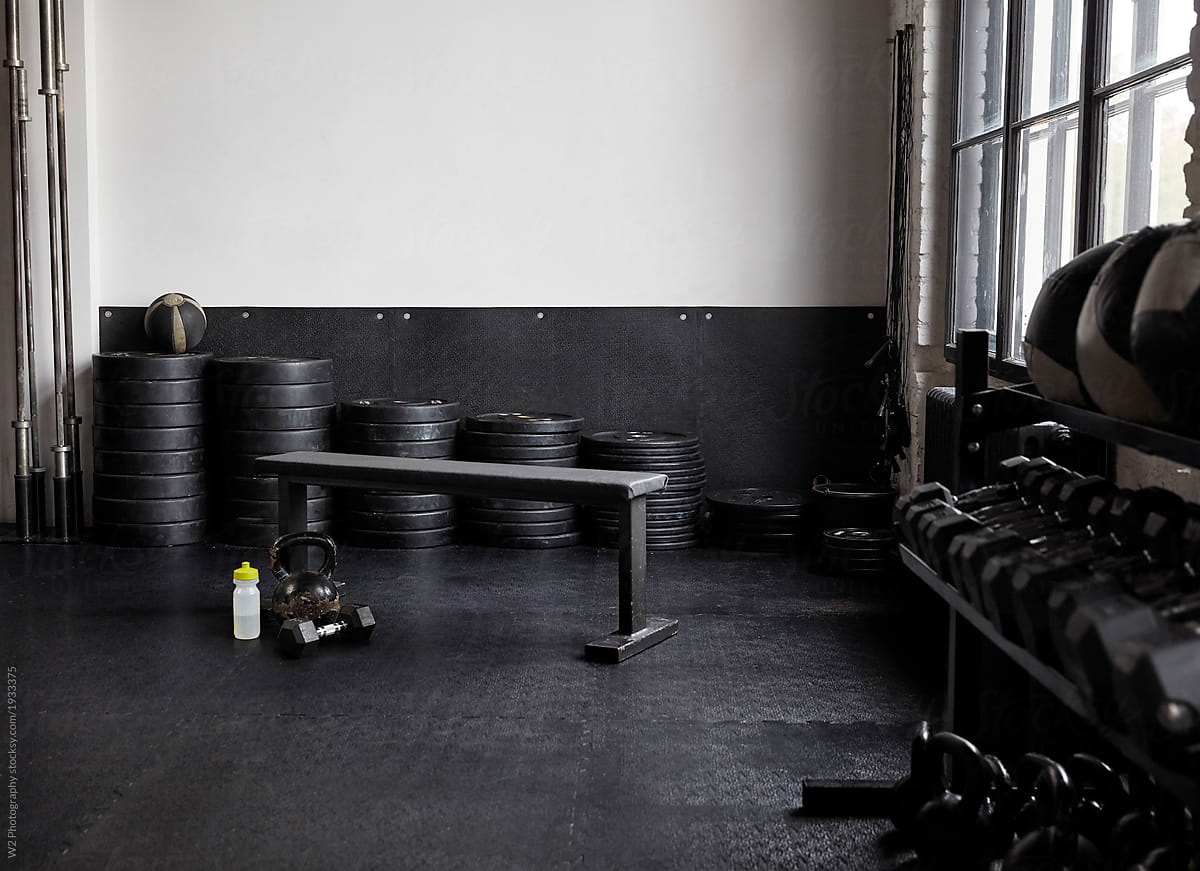 A weight bench in a empty corner of a gym. stocksy united