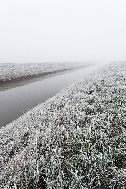 Frost on a riverbank with river running through the scene by Paul Phillips for Stocksy United