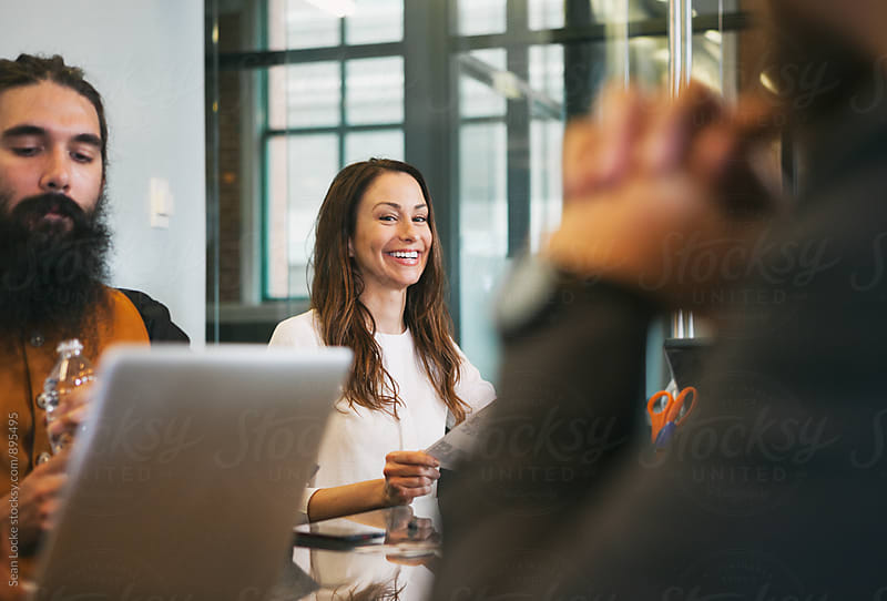 Office: Pretty Woman Laughs During Meeting In Conference Room by Sean Locke for Stocksy United