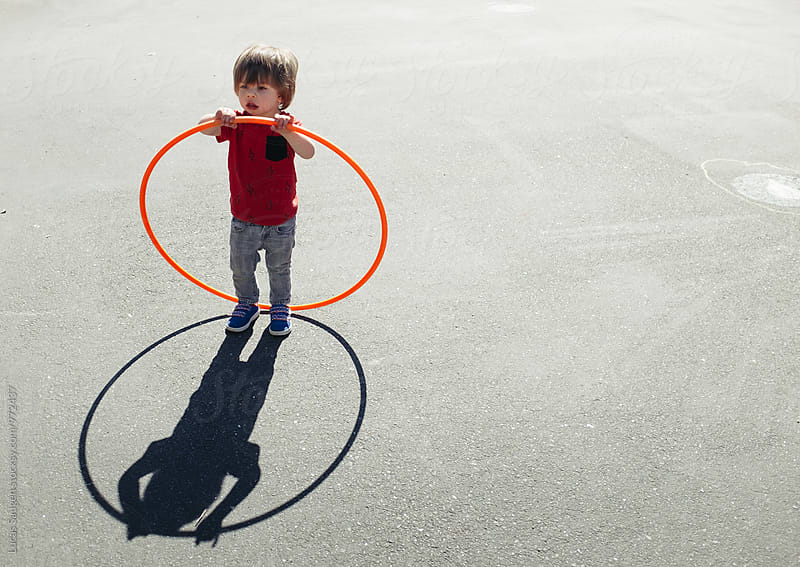Boy plays with a hula hoop on a asphalt playground. by Lucas Saugen for Stocksy United