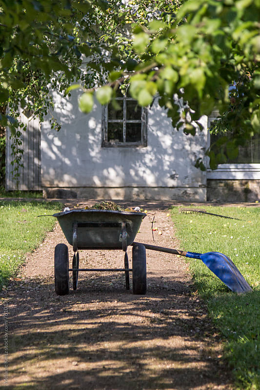 Wheelbarrow and shovel on a garden path by Melanie Kintz for Stocksy United