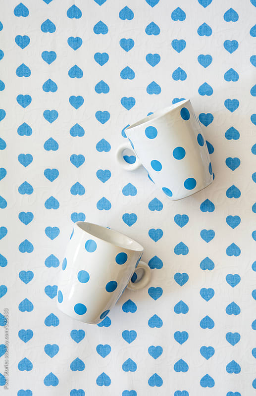 Blue-dotted cups on blue hearts cloth by Pixel Stories for Stocksy United