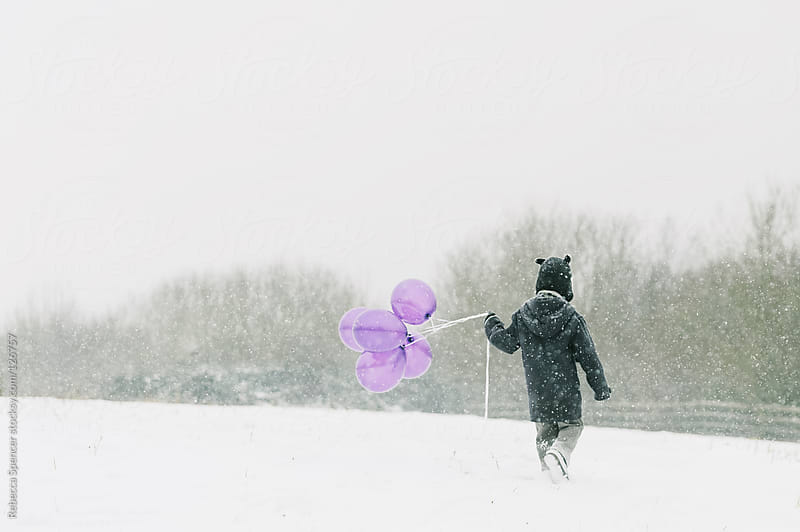 Child walking in falling snow by Rebecca Spencer for Stocksy United