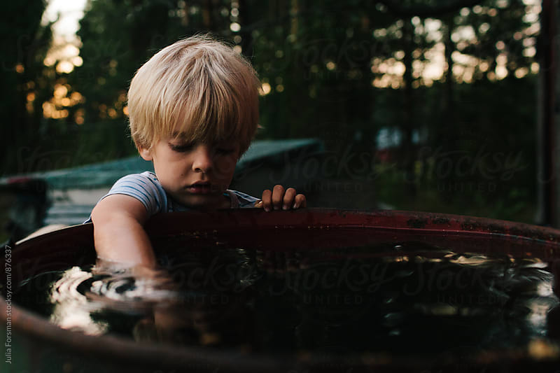 Boy puts his arm into collected rainwater while playing a t dusk. by Julia Forsman for Stocksy United