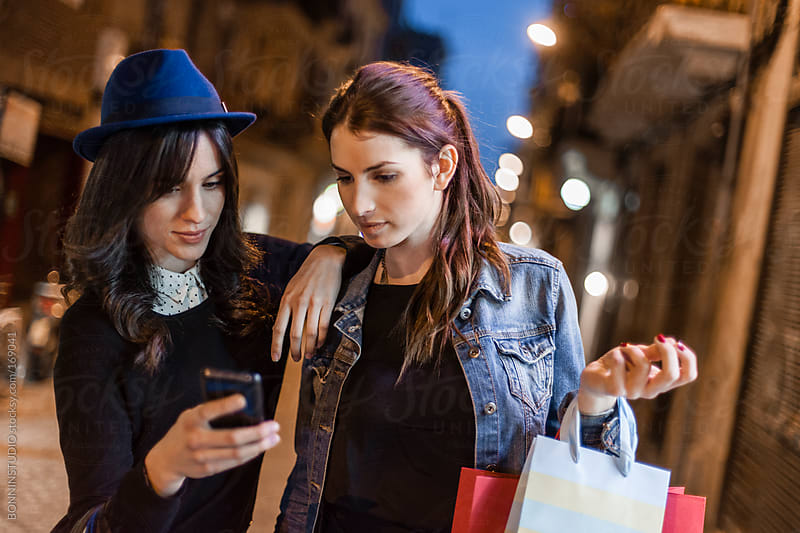 Two young shopping women looking a smartphone on the cityscape. Online shopping. by BONNINSTUDIO for Stocksy United