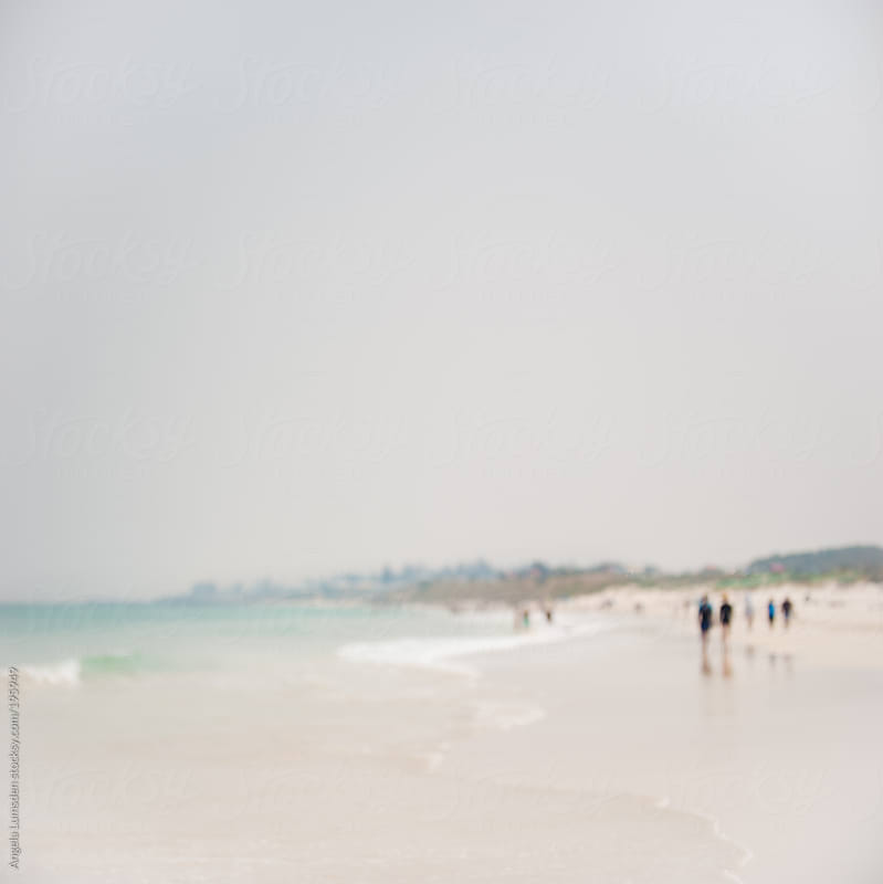 Blurred image of people walking on a beach on a hazy day by Angela Lumsden for Stocksy United