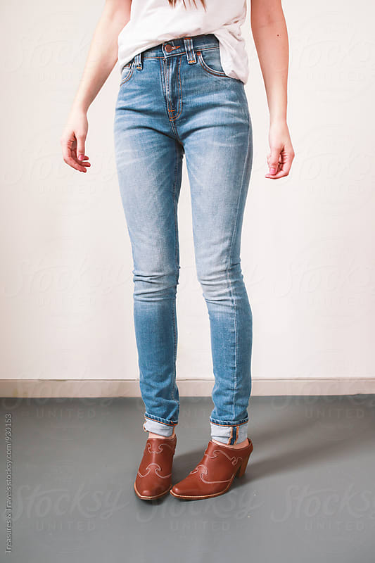 woman standing in denim against a white wall by Treasures & Travels for Stocksy United
