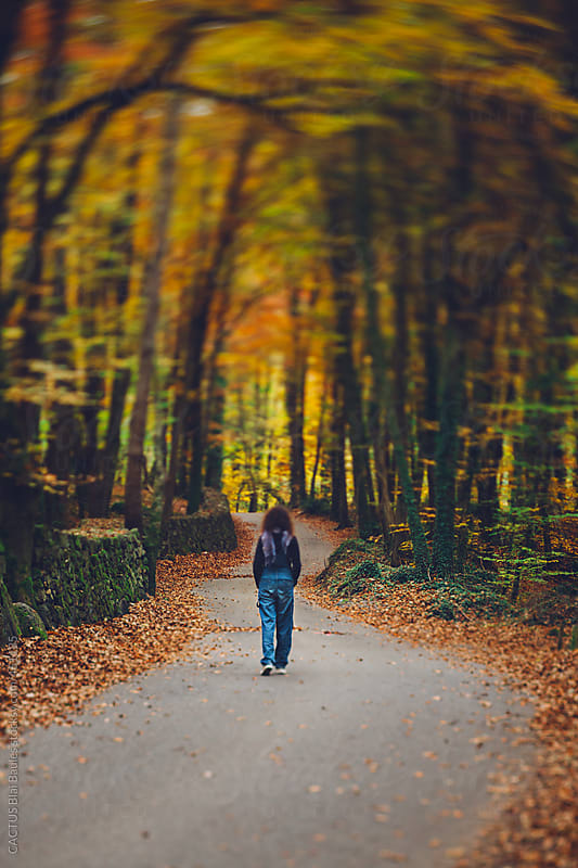 Woman walking on the road in the autumn forest. by CACTUS Blai Baules for Stocksy United