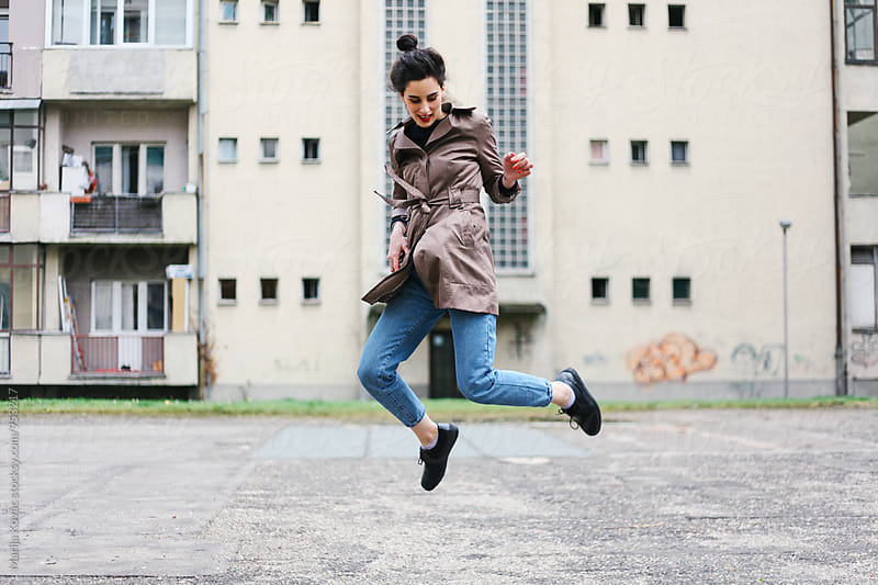 Happy woman jumping outdoor by Marija Kovac for Stocksy United