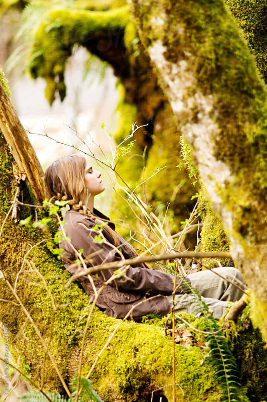 A young girl sitting in the forest holding bow and arrow  by Tana Teel for Stocksy United