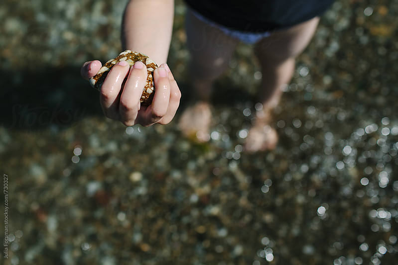 A child holds a stone he has picked up on the beach. by Julia Forsman for Stocksy United