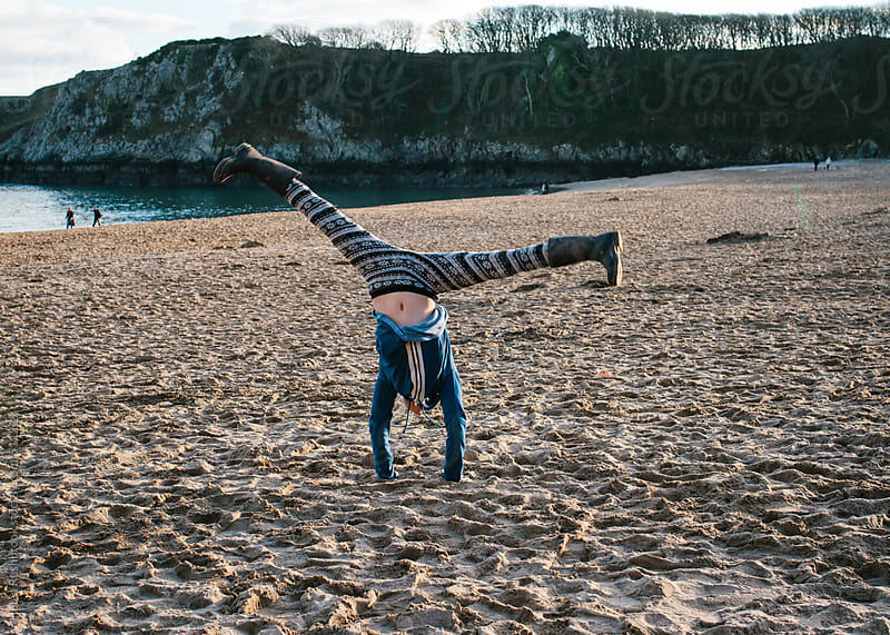 A little girl doing a hand stand on a beach. by Helen Rushbrook for Stocksy United