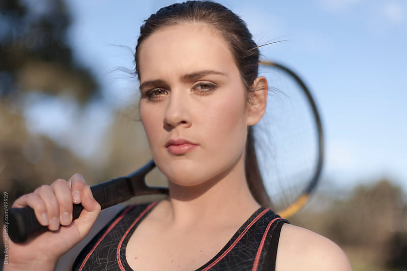 Young female tennis player with a racquet draped over her shoulder by Ben Ryan for Stocksy United