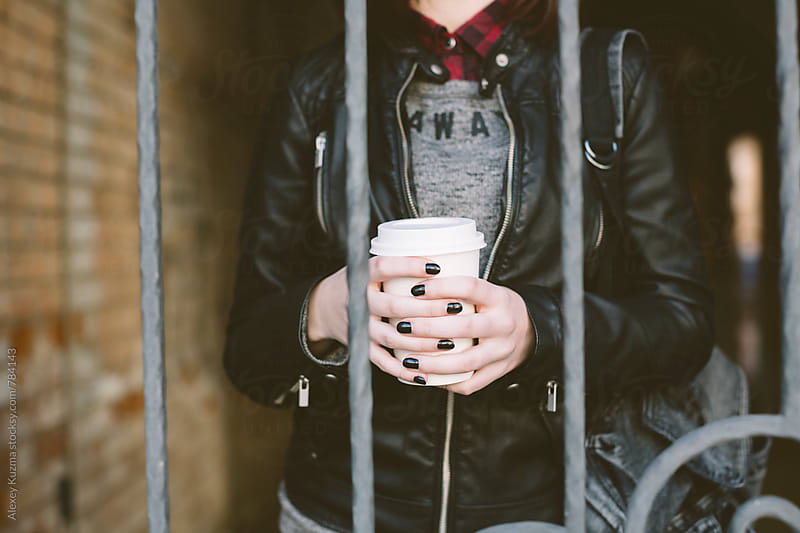 young woman with coffee on the street by Alexey Kuzma for Stocksy United