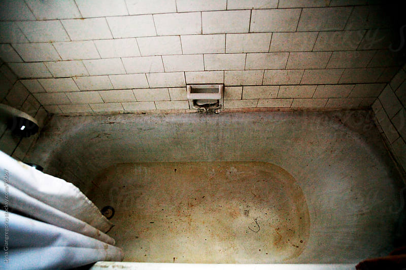Dirty and abandoned  empty bathtub  by Dina Giangregorio for Stocksy United