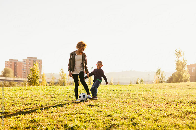 Mother and her son playing football in the park.  by BONNINSTUDIO for Stocksy United