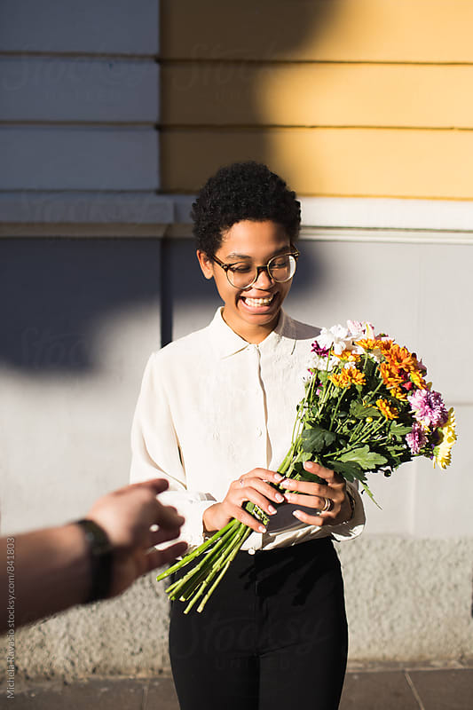 Smiling woman receiving a bouquet of flowers by michela ravasio for Stocksy United