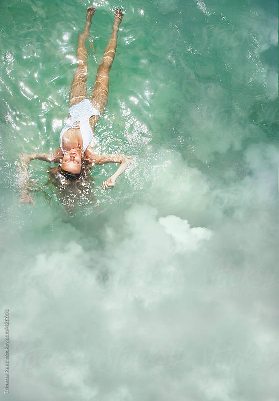 Woman floating in the ocean with clouds by Trinette Reed for Stocksy United