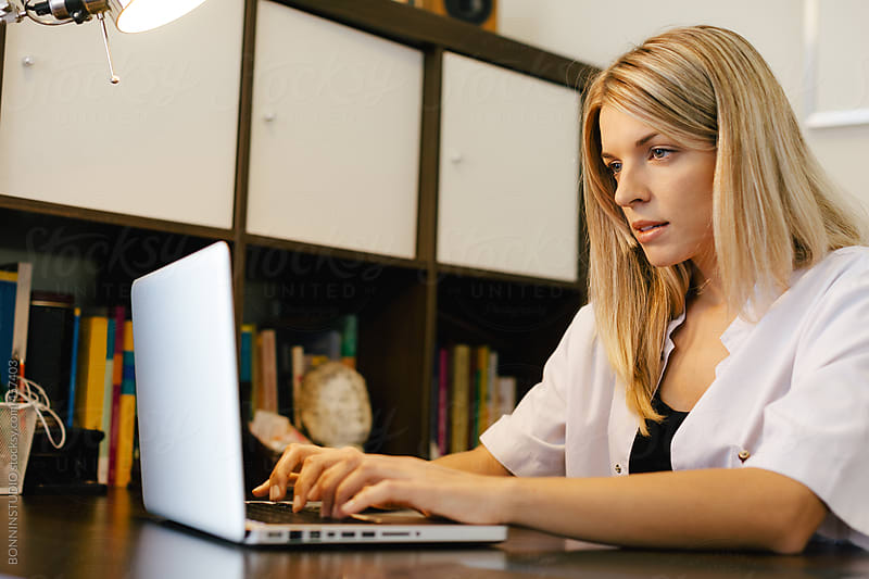Young medical woman working with laptop on a workspace. by BONNINSTUDIO for Stocksy United