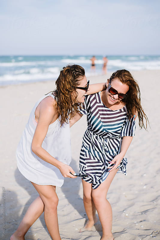 Two friends laughing at the beach by Pixel Stories for Stocksy United